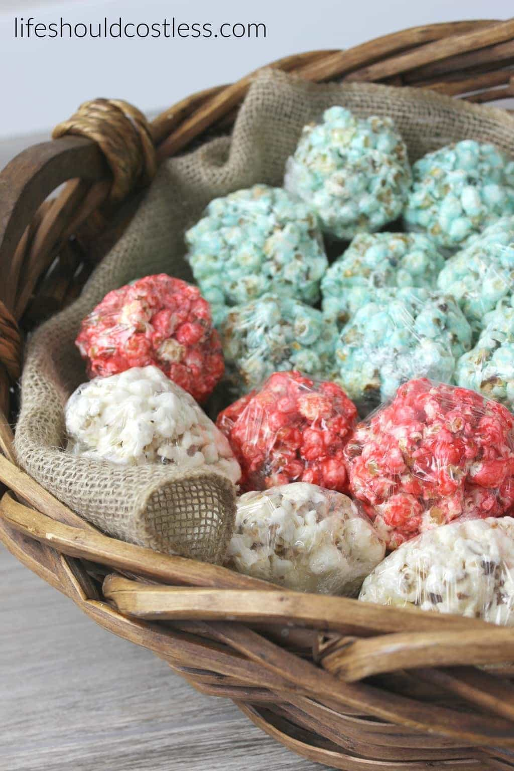 Red white and blue patriotic flag popcorn balls in large basket with burlap liner. {lifeshouldcostless.com}