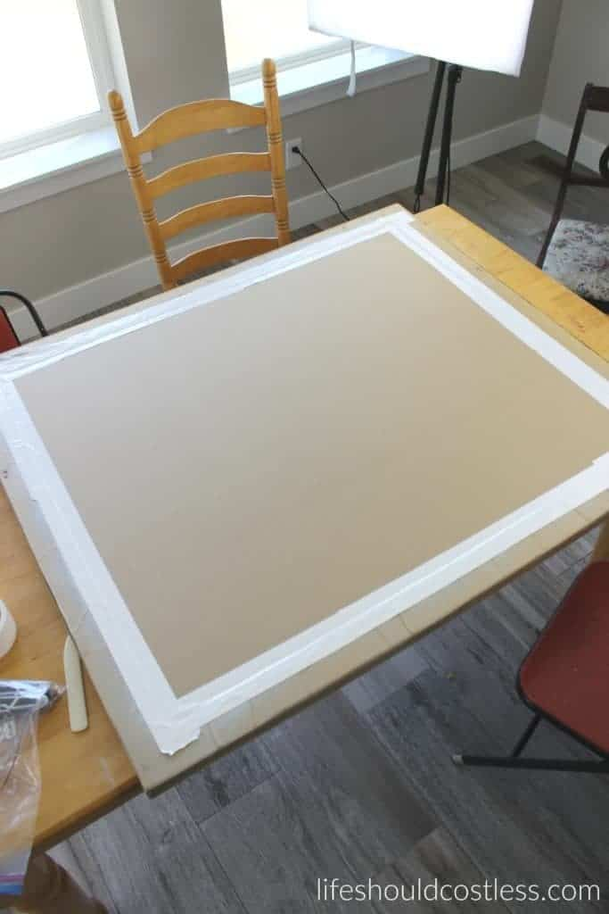 Huge print in frame turned faux antique mirror. White duct tape to hold on the cardboard on the back.