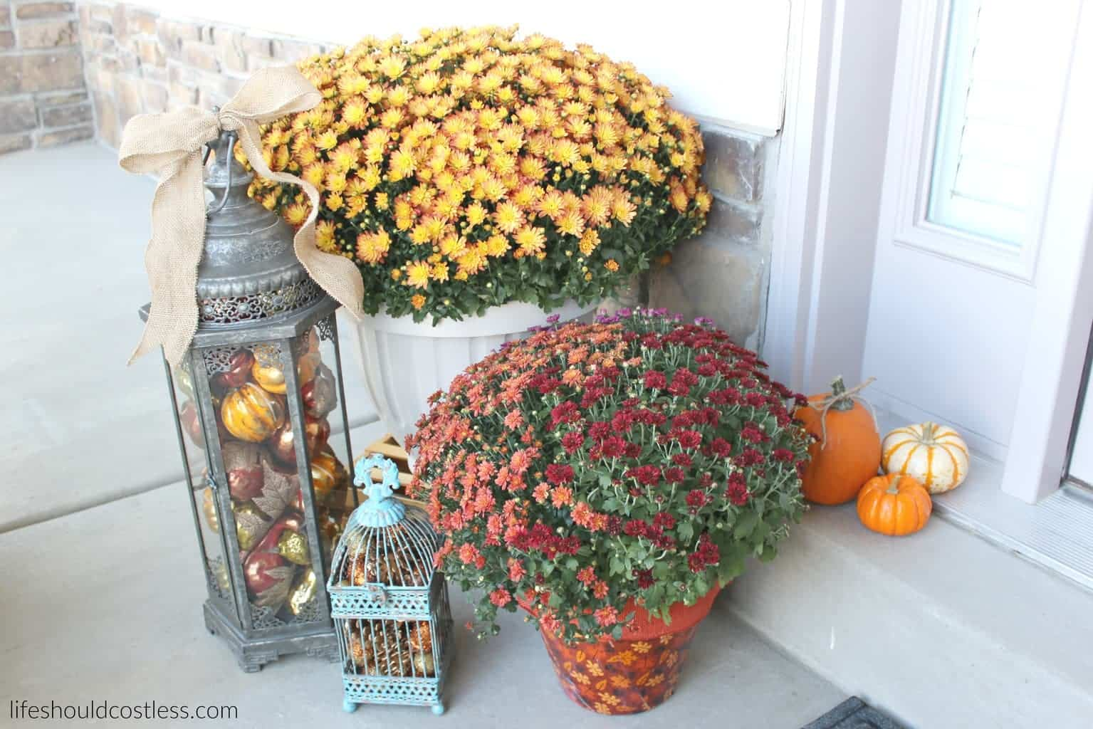 Rustic fall porch decor reveal. See this post and many more popular decor pins at lifeshouldcostless.com. Lantern filled with fall decor.