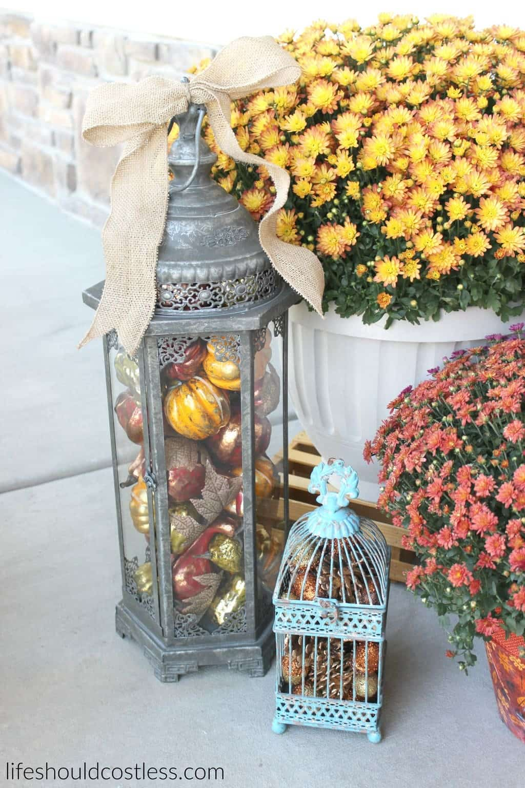 Rustic fall porch decor reveal. See this post and many more popular decor pins at lifeshouldcostless.com. Lantern and bird cage filled with fall decor.