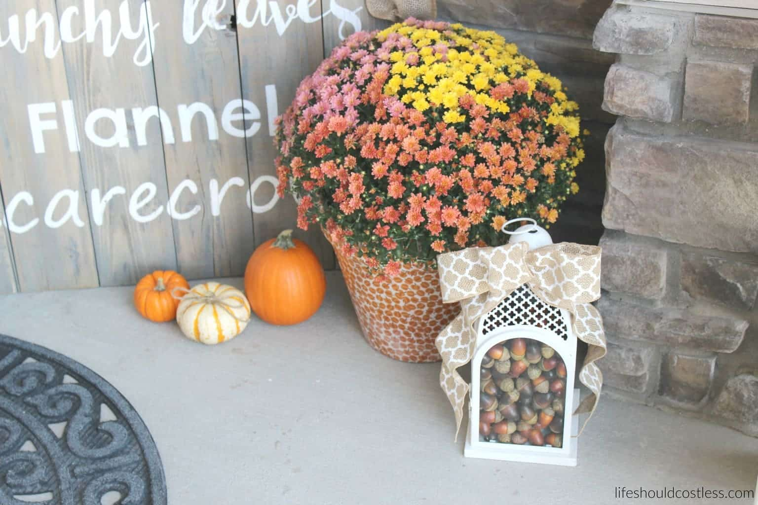 Rustic fall porch decor reveal. See this post and many more popular decor pins at lifeshouldcostless.com. Lantern filled with acorns.