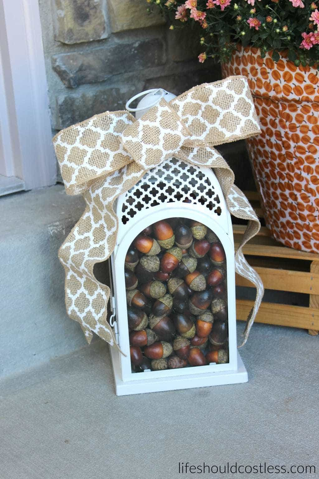 Fall lantern filled with acorns. Burlap bow. Rustic/Farmhouse decor idea.